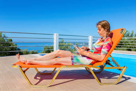 Middle aged dutch woman lying on orange sunlounger reading tablet near pool