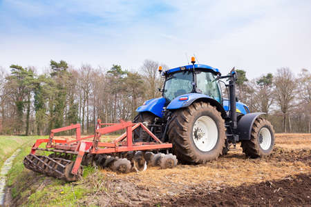 Dutch tractor tills the ground with a harrow in spring season Reklamní fotografie