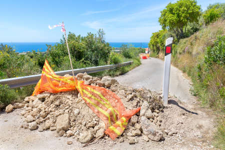 Blockage with stones on coastal road in Greek Kefalonia Stock Photo
