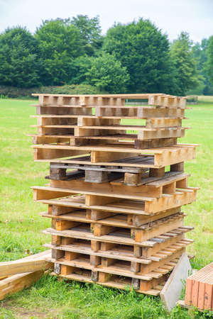 High stack of wooden pallets in Dutch pasture