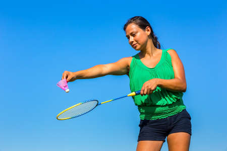 Young Colombian woman serve with badminton racket and shuttle in front of blue sky