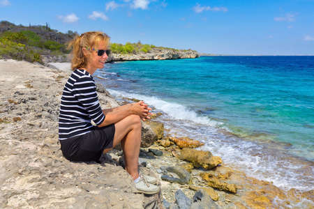 Caucasian middle aged woman sits at coast of Netherlands Antilles Reklamní fotografie