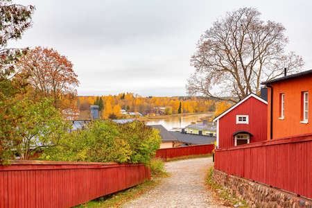 Finnish landscape with red wooden fences and houses along the river in Porvo Reklamní fotografie