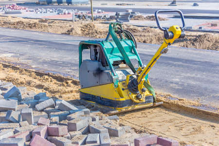 Vibrating machine on sand next to new street in road construction Reklamní fotografie