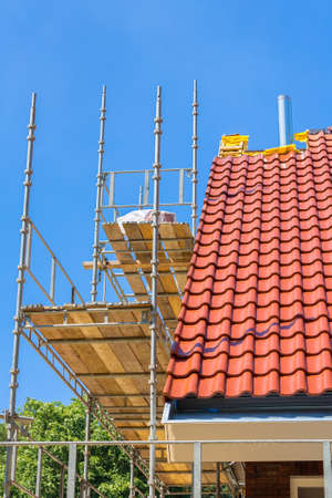 New roof tiles on house with scaffolding and blue sky Reklamní fotografie