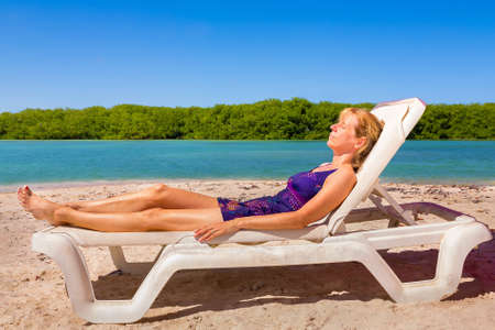 Caucasian woman sunbathes on beach bed by the sea on island Bonaire Reklamní fotografie