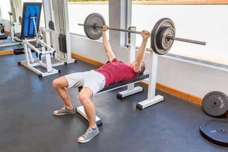 Young dutch man bench press with barbell in fitness room Reklamní fotografie