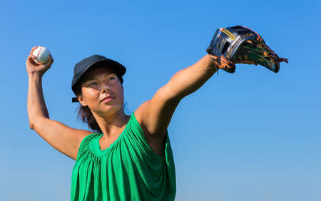 Colombian woman with baseball glove and cap throwing baseball in blue sky