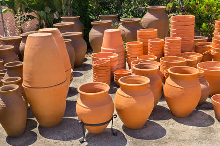 Many big orange clay vases outdoors at portuguese pottery shop