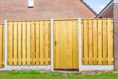 New dutch wooden fence construction with porch and stone wall