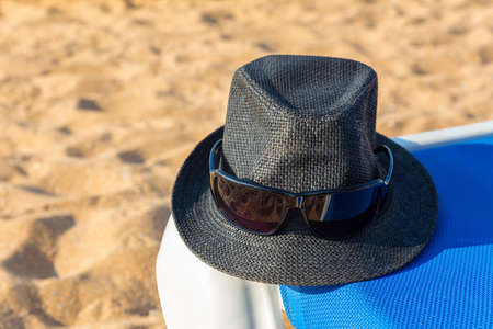 Gray sun hat and sunglasses on blue beach bed at coast