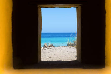 look through window in window with blue sea view on island Bonaire