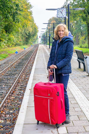 Caucasian woman with red suitcase waitng on dutch railway station