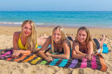 Three pretty caucasian girls ly on beach sunbathing at coast with blue sea Standard-Bild