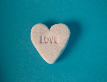 cupido: In a piece of heath shaped candy the word love has been written in it.