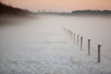 disappears: A fence on a field filled with snow disappears into mist.