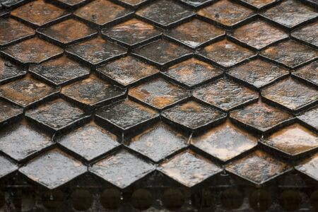 rooftiles: During a rain shower in Thailand, water is dripping down from the roof tiles.