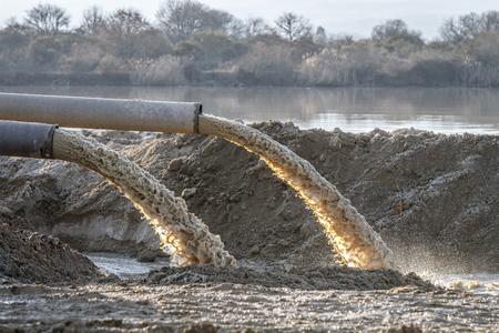 efluentes industriales, ductos que descargan desechos industriales líquidos en un río