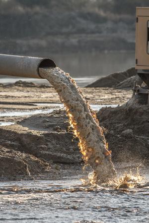 industrial effluent, pipeline discharging liquid industrial waste into a river Stock Photo - 94068866