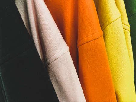 Multi colored sweatshirts on the coat rack Foto de archivo