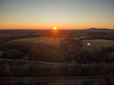 The sun sets over Clarksburg, Montgomery County, Maryland. Sugarloaf Mountain is to the right.
