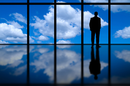man looking out: Business Man Looking Out of High Rise Office Window at Blue Sky and Clouds