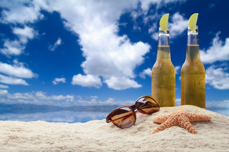 Two cold beers with lime in a beautiful tropical beach setting with sunglasses and starfish