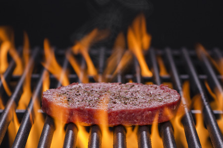meat on grill: Raw hamburger patty on a hot flaming BBQ grill