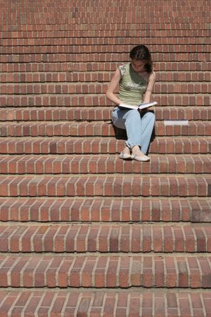 Young lady reads a book sitting on stairs Banco de Imagens