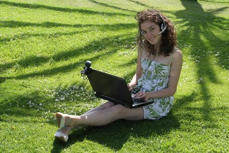 Young lady chats with friends on her laptop computer outdoor