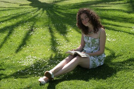 Young lady reads a book sitting in the park