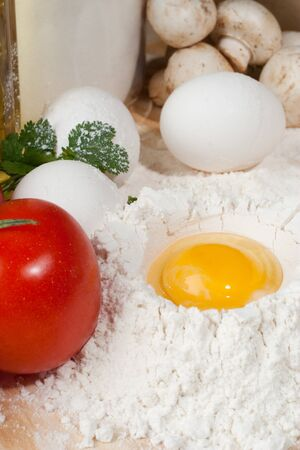 Heap of flour with raw egg on wooden table top Stock Photo - 22037422