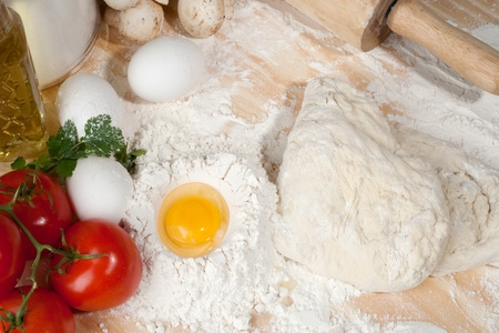 Heap of flour with raw egg on wooden table top Stock Photo - 22037423