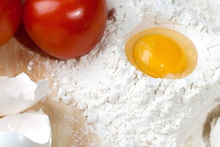 Heap of flour with raw egg on wooden table top Stock Photo