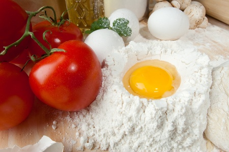 table top: Heap of flour with raw egg on wooden table top Stock Photo