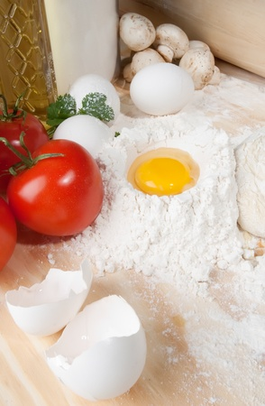 Heap of flour with raw egg on wooden table top Stock Photo - 22037436