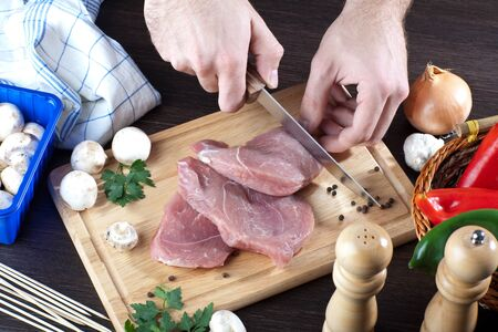 Person cooking raw pork meat with some veggies  Stock Photo