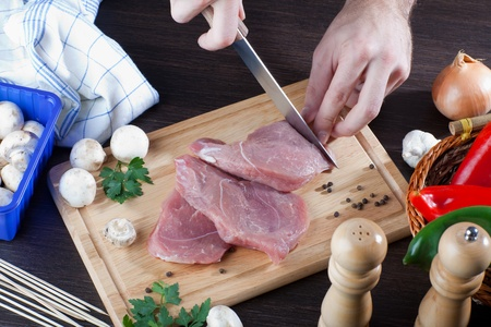 Person cooking raw pork meat with some veggies  Archivio Fotografico