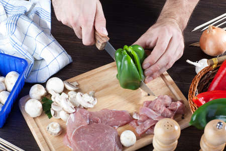 Person cooking raw pork meat with some veggies  Фото со стока