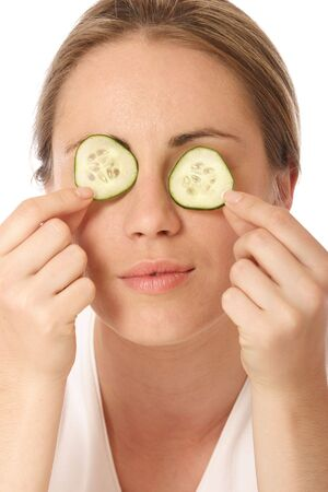 Young woman holding cucumber in front of her eyes photo