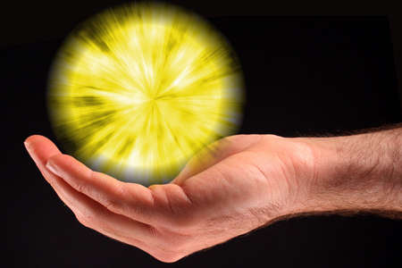 psychisch: Een hand met een gele bol van licht tegen een zwarte achtergrond.  Stockfoto