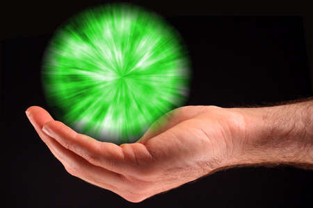 A hand holding a green ball of light against a black background.