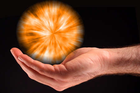 A hand holding an orange ball of light against a black background. Stock Photo
