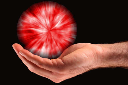 A hand holding a red ball of light against a black background.