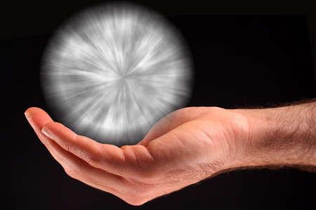 Ręka trzyma piłkę białego światła na czarnym tle.