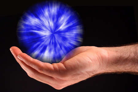 A hand holding a blue ball of light against a black background.