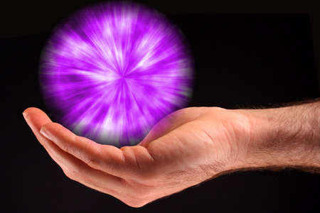 A hand holding a purple ball of light against a black background. Stock Photo