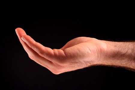 Eine schalenförmige Hand vor schwarzem Hintergrund.