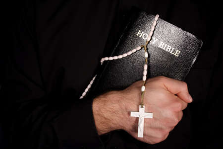 A priest holding The Holy Bible and a rosary.