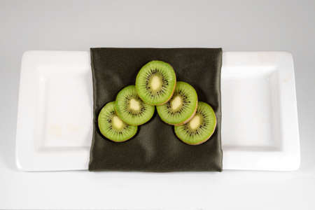 An arrangement of kiwi on a green decorative napkin on a white plate with a white background.